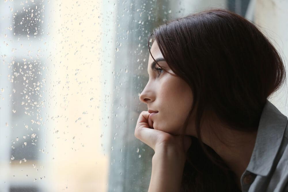 mujer-mirando-con-cara-de-tristeza-por-la-ventana